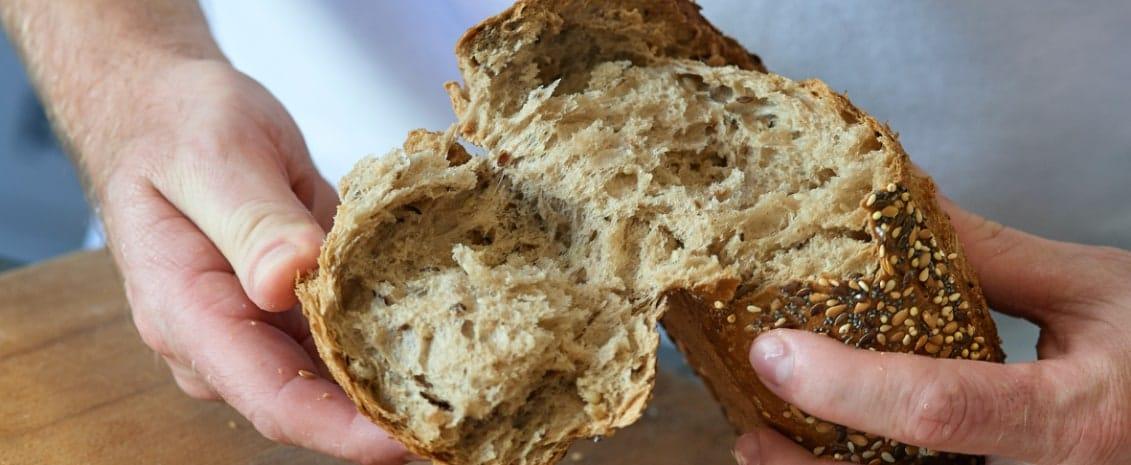 miche de pain coupée en deux à la main